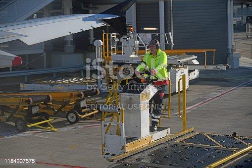 Brisbane, Australia, July 21, 2019: An unidentified luggage handler at Brisbane International airport steers his luggage handling machine towards the aeroplane, ready to unload its cargo.