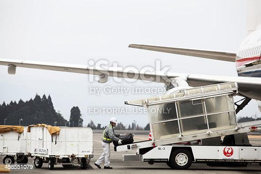 Kagoshima, Japan - January 28, 2012: A luggage handler loading a China Eastern Airlines airplane at the International Terminal of Kagoshima Airplort.