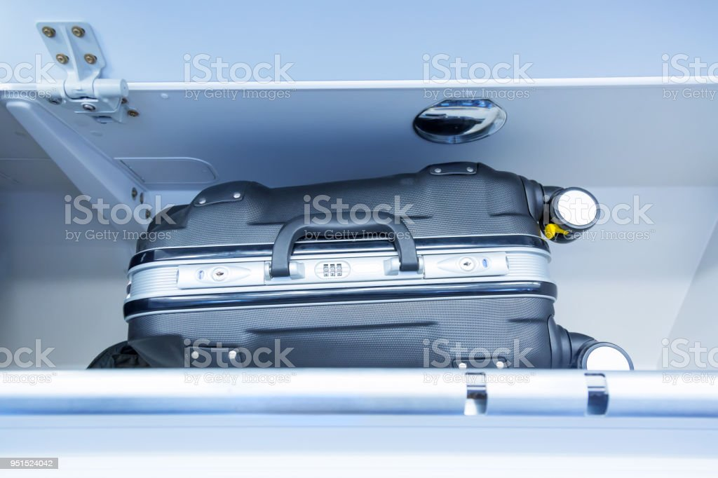 Luggage shelf with luggage suitcase in an airplane. Aircraft interior. Travel concept. Luggage shelf with luggage suitcase in an airplane. Aircraft interior. Travel concept Air Vehicle Stock Photo