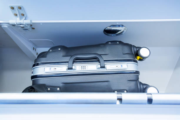Luggage shelf with luggage suitcase in an airplane. Aircraft interior. Travel concept. Luggage shelf with luggage suitcase in an airplane. Aircraft interior. Travel concept carry on luggage stock pictures, royalty-free photos & images