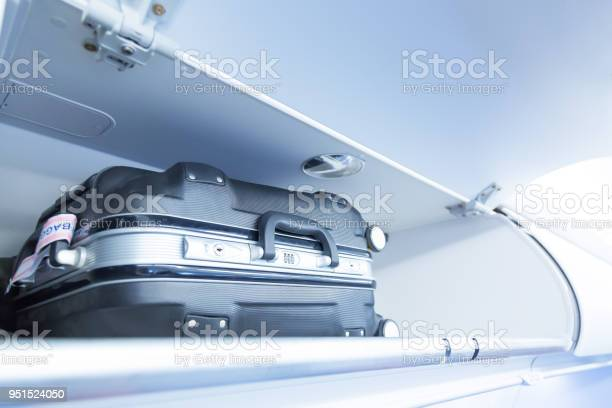 Luggage Shelf With Luggage Suitcase In An Airplane Aircraft Interior Travel Concept Stock Photo - Download Image Now