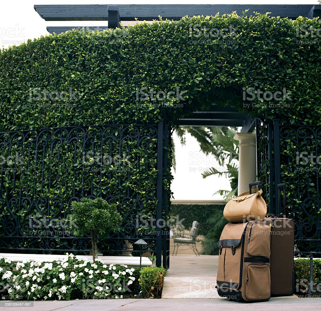 Luggage sitting in front of hotel gate stock photo