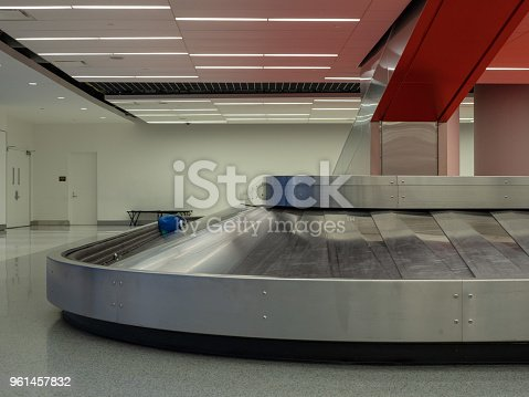 istock Luggage sitting on baggage claim carousel in airport 961457832