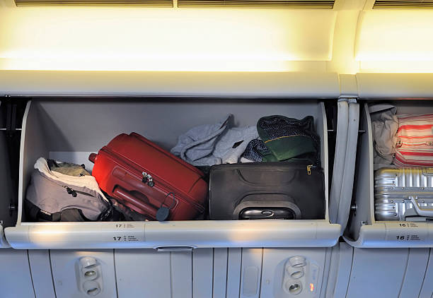 luggage storage Carry-on luggage in overhead storage compartment on commercial airplane. carry on luggage stock pictures, royalty-free photos & images
