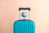 Suitcase and world globe model on pastel beige background minimal creative travel concept