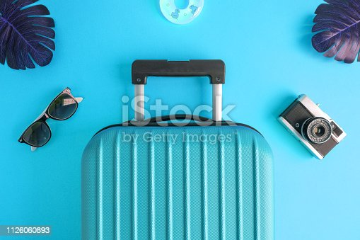 istock Luggage with summer vacation accessories on turquoise. 1126060893