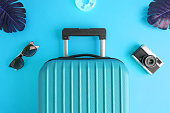 Flat lay of suitcase, monstera leaves, sunglasses, retro photo camera and inflatable pool floats against light blue background minimal creative summer travel vacation concept.