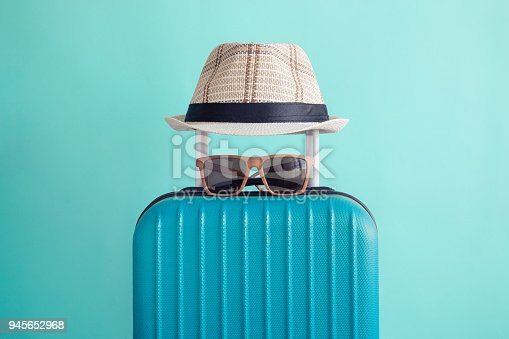 Suitcase with hat and sunglasses on pastel green background minimal creative travel concept