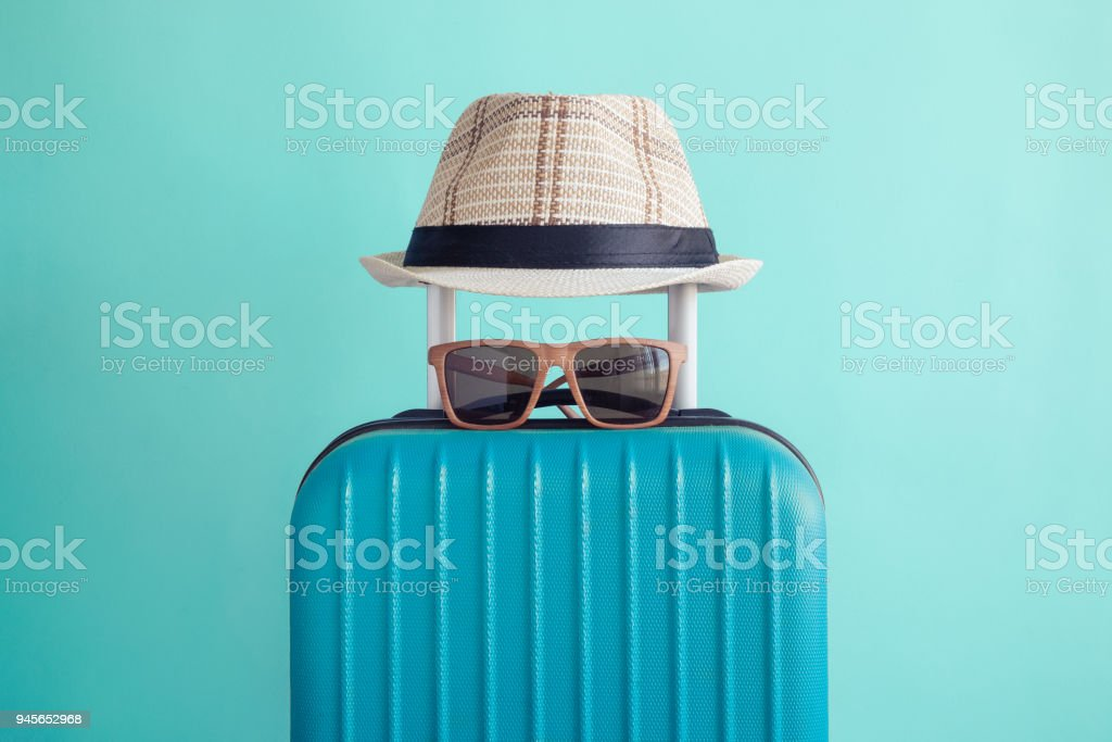 Luggage with woven beach hat and sunglasses on green background minimalistic vacation concept stock photo