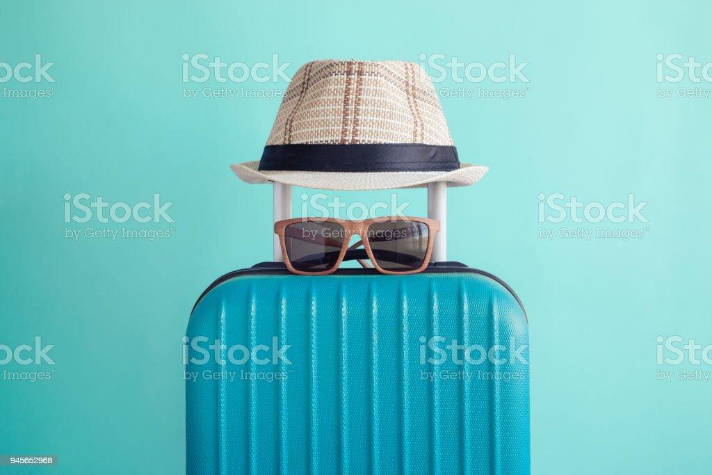 Equipaje con tejido playa sombrero y gafas de sol en concepto de vacaciones minimalista de fondo verde - foto de stock
