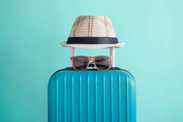 luggage with woven beach hat and sunglasses on green background minimalistic vacation concept - vacations stock pictures, royalty-free photos & images