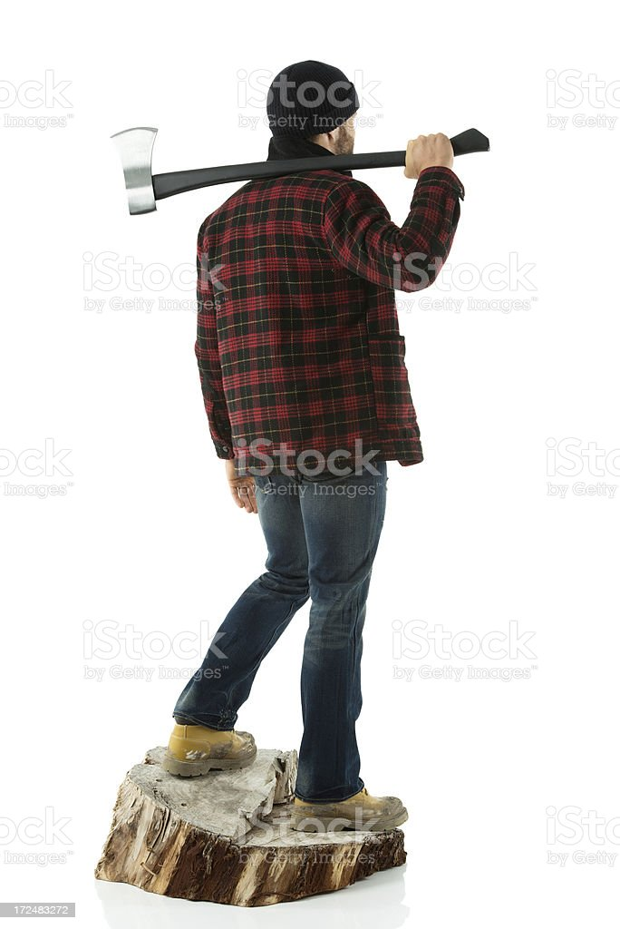 Lumber standing on a tree stump with an axe royalty-free stock photo