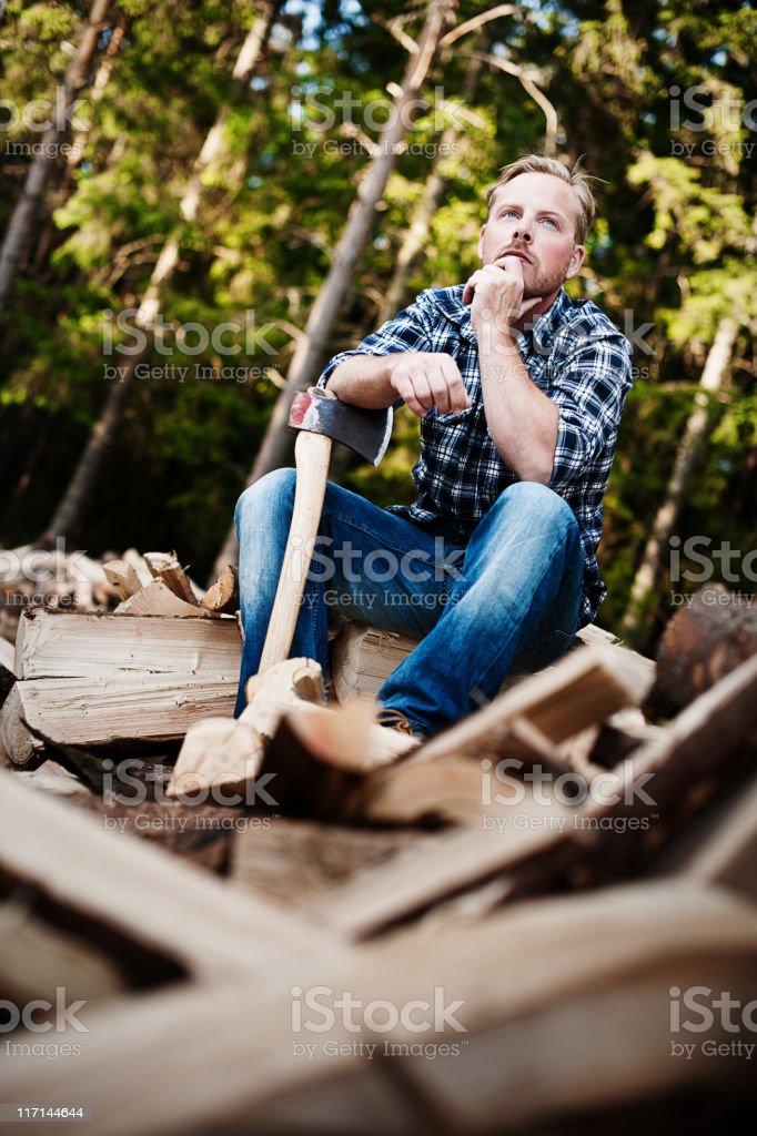 Lumberjack on top of wood pile royalty-free stock photo