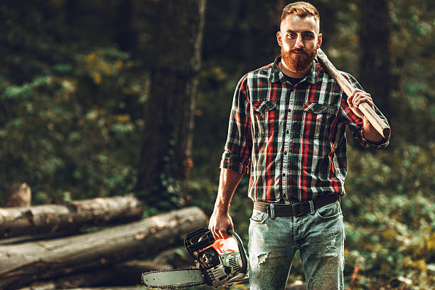 Lumberjack Lumberjack worker standing in the forest with axe and chainsaw forester stock pictures, royalty-free photos & images