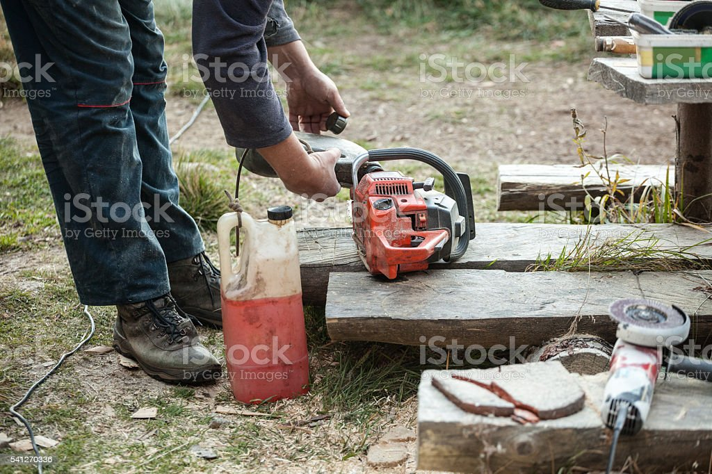 Lumberjack refilling chainsaw with machine oil stock photo