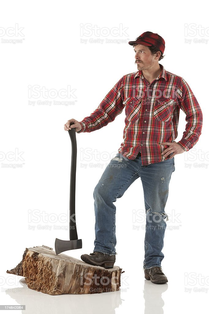 Lumberjack standing on a tree stump with an axe royalty-free stock photo