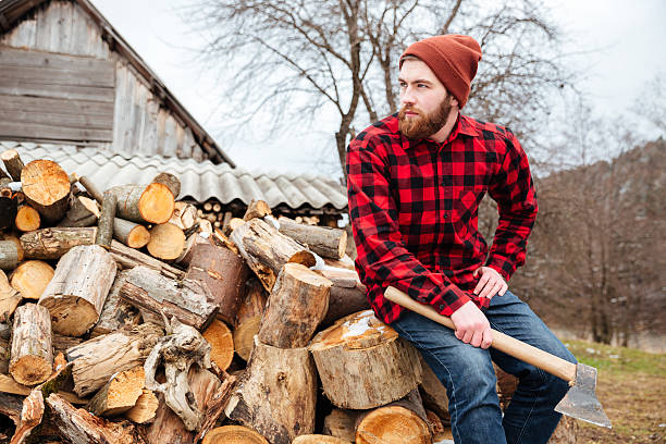 Lumberjack with axe resting outdoors Lumberjack with axe resting outdoors and looking away lumberjack stock pictures, royalty-free photos & images