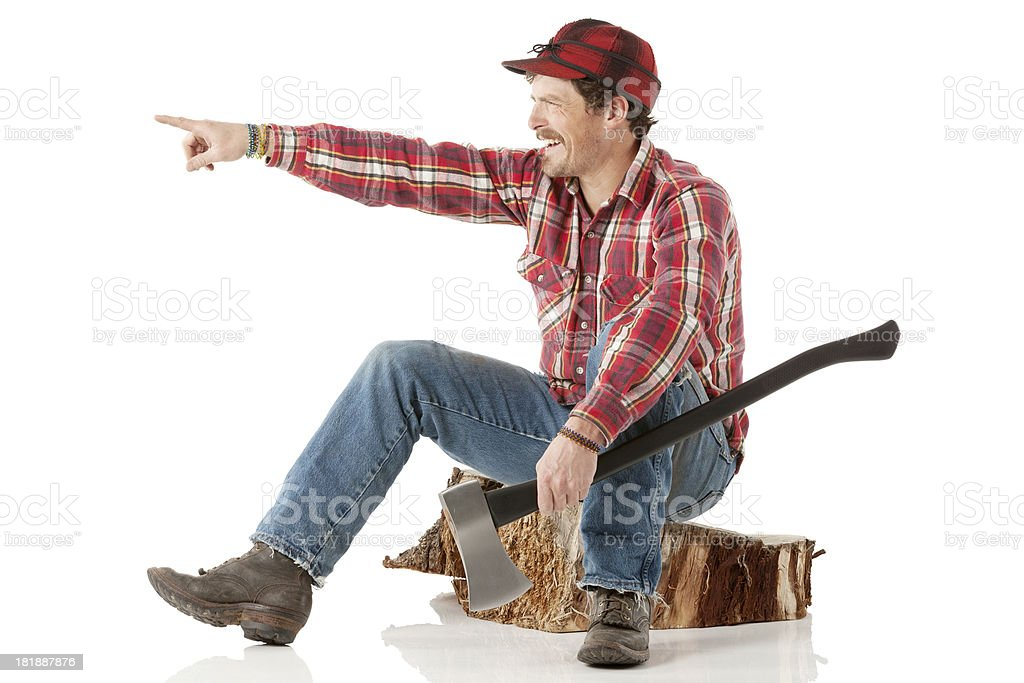 Lumberman sitting on a tree stump and pointing royalty-free stock photo