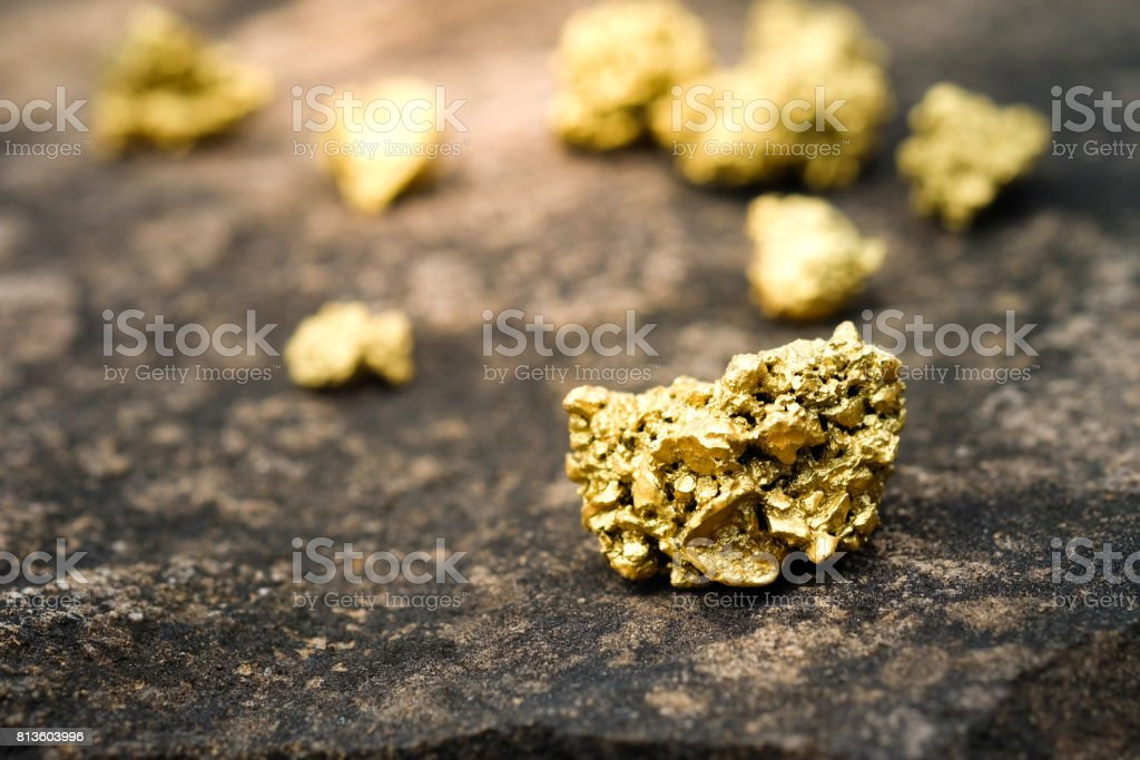 A lump of gold on a stone floor stock photo
