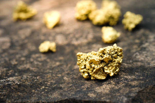 a lump of gold on a stone floor - gold mine stock photos and pictures