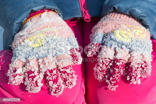 Lumps of frozen snow on woolen gloves in the winter