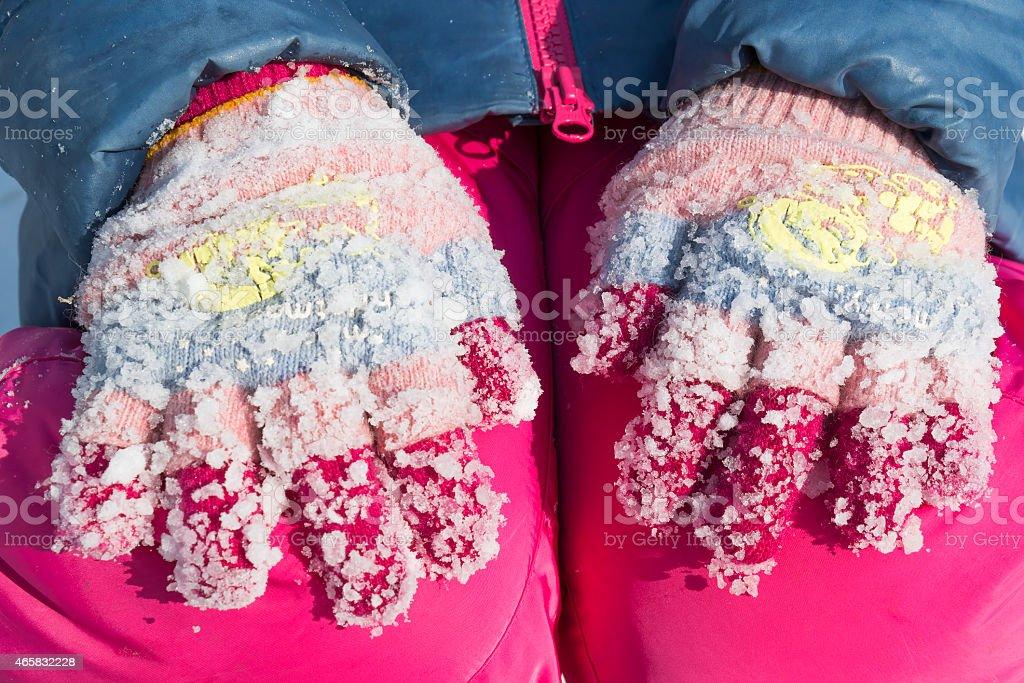 Lumps of frozen snow on woolen gloves stock photo