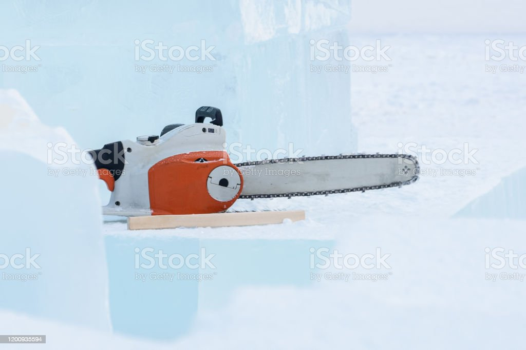 Lumps of ice and a chainsaw. Winter Ice Sculpture Festival Lumps of ice and a chainsaw. Winter Ice Sculpture Festival Activity Stock Photo