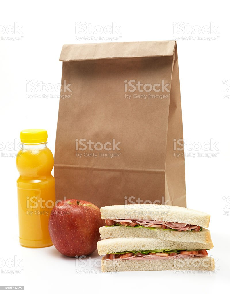 Lunch bag with sandwich, apple and orange juice stock photo