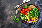 Lunch bowl with vegetables,beans and chicken meat on a dark slate,stone or metal background.Top view.