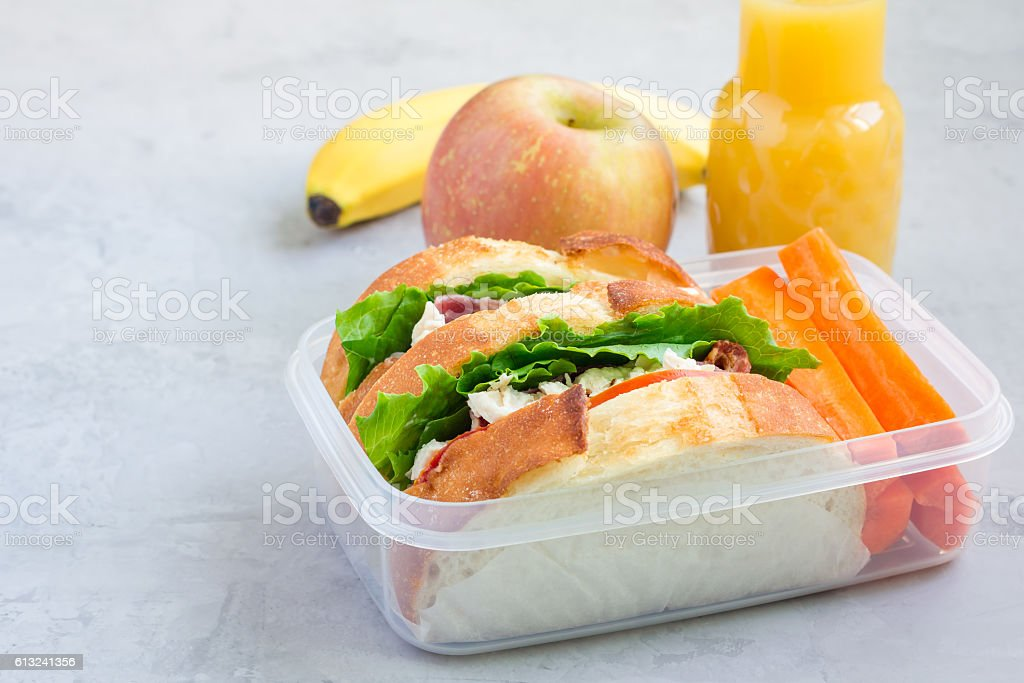 Lunch box with chicken salad sandwiches and carrot sticks, horizontal stock photo