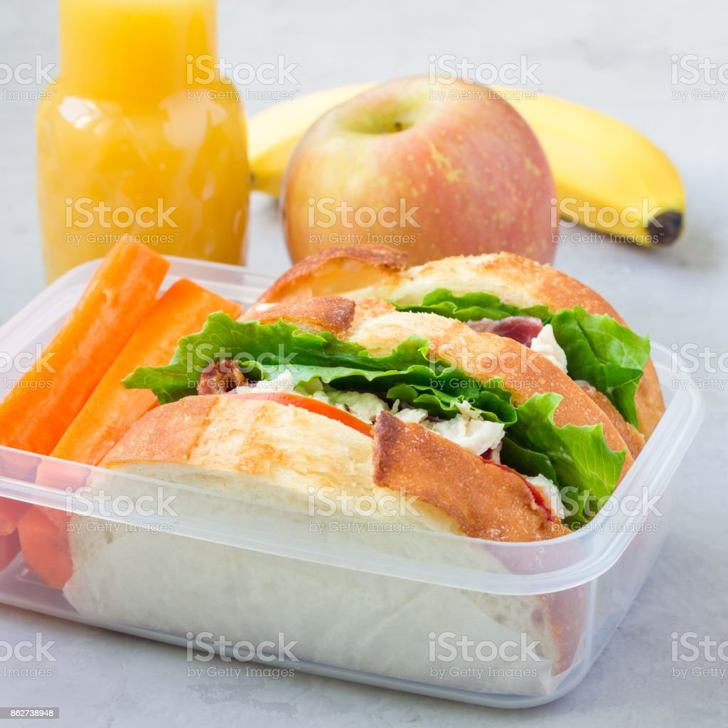 Lunch box with chicken salad sandwiches, served with carrot sticks. Fruits and juice on background, square format stock photo