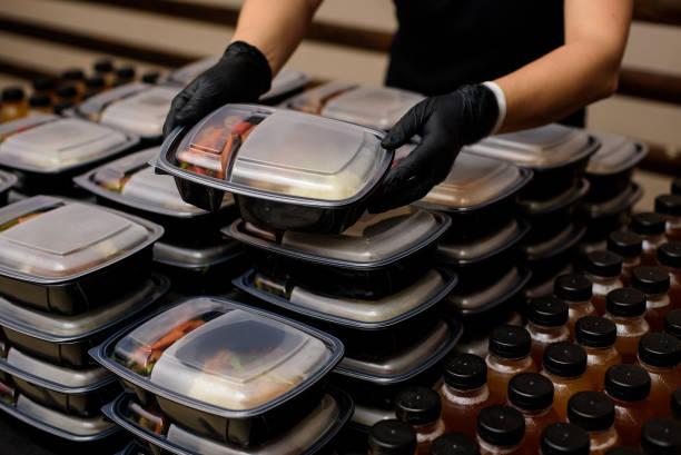 de doos van de lunch met voedsel in de handen. catering - portie stockfoto's en -beelden