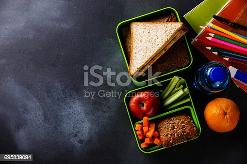 istock Lunch box with Sandwiches, bottle of water and school supplies 695839094