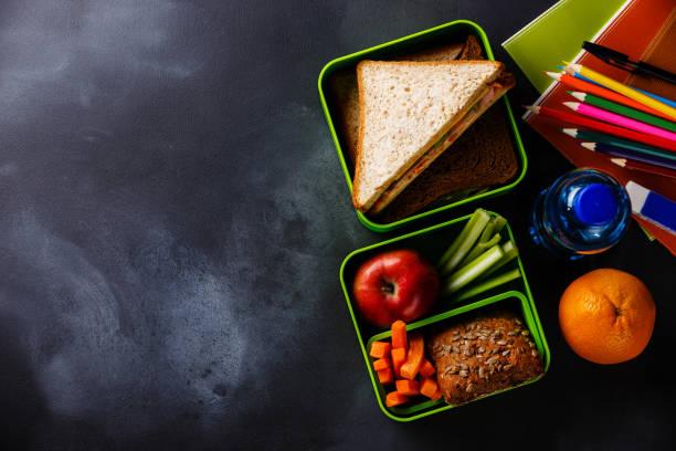 lunch låda med smörgåsar, flaska vatten och skolmaterial - lunchlåda bildbanksfoton och bilder