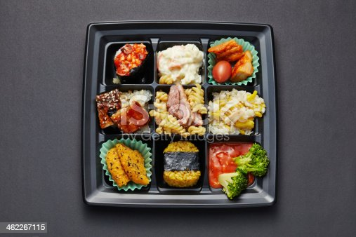 istock Lunch box with sushi and rolls isolated on black 462267115
