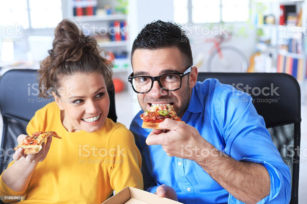 Collegues eating pizza at the office. Young man with eyeglasse and...