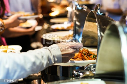 546450250istockphoto Lunch food buffet catering party with hand of people enjoying 1179066211