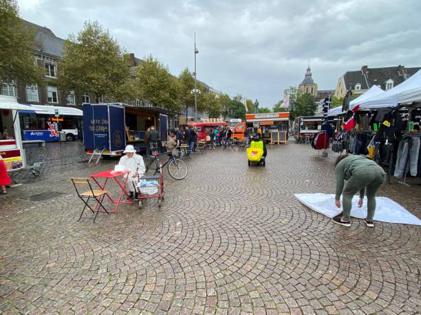 Lunch in Corona style Maastricht, the Netherlands, - September30, 20204. Senior woman having lunch in corona social distance on the market place. outdoor dining raining stock pictures, royalty-free photos & images