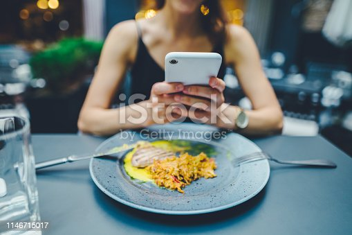Close-up of woman in restaurant texting on phone