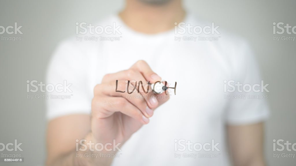 Lunch, man writing on transparent screen stock photo