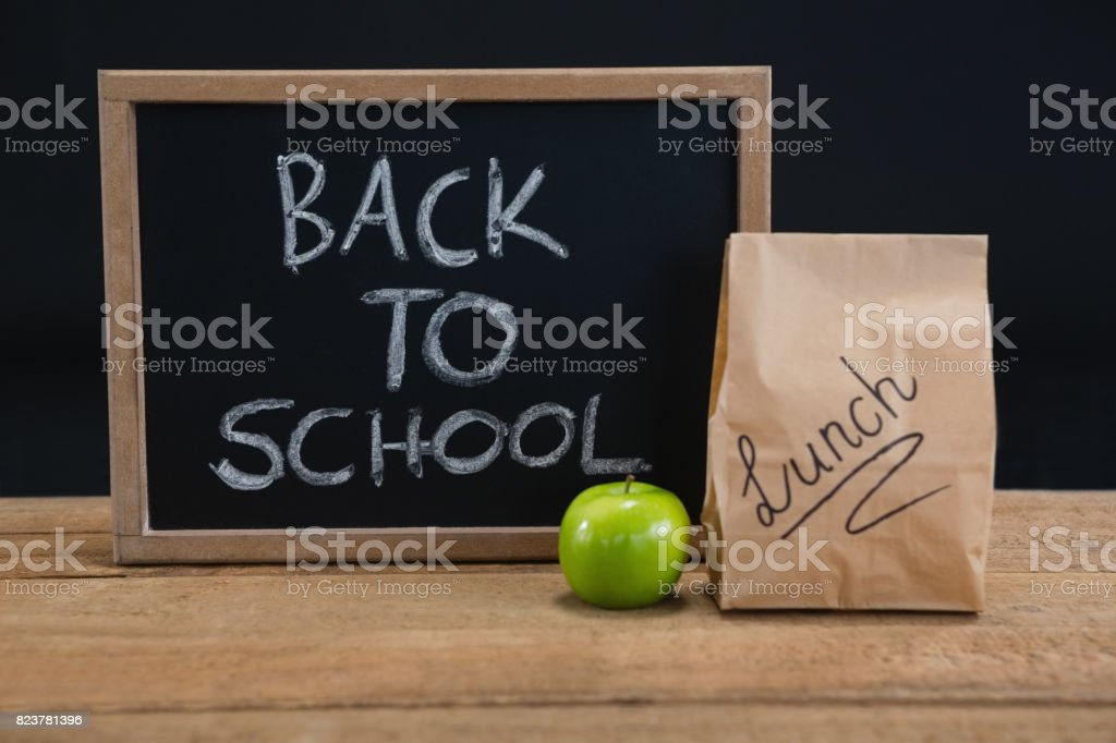 Lunch paper bag, green apple and slate with text back to school on wooden table stock photo