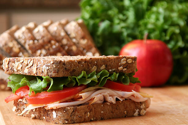 Lunch Healthy sandwhich made with whole grain bread, lettuce, tomato, cheese, and roasted chicken slices. whole wheat stock pictures, royalty-free photos & images