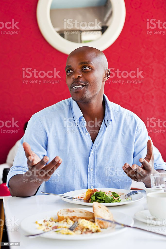 Lunch A handsome african talking and gesturing during lunch in the restaurant. Adult Stock Photo