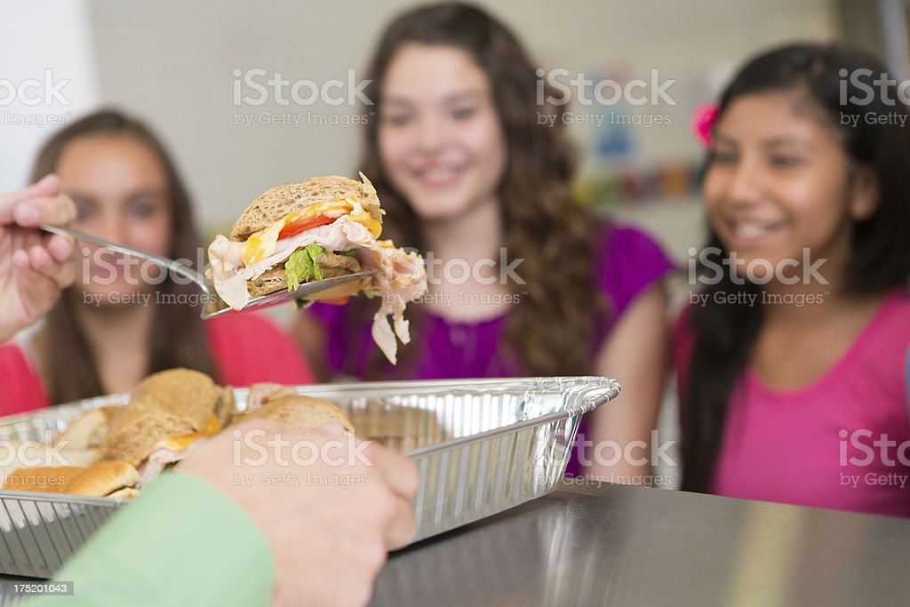 Lunch server showing sandwich to students in school cafeteria royalty-free stock photo