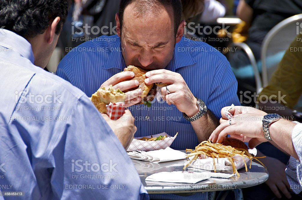 Lunch time outdoors. Male bites into hamburger. royalty-free stock photo