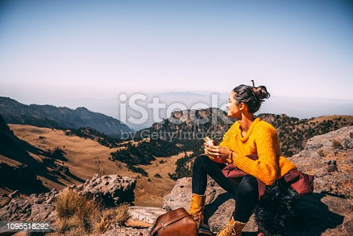 Tired Latin woman making a launch break. She is hiking at Popocatepetl volcano in Mexico