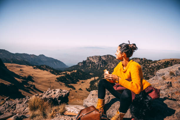 Lunch time. Tired Latin woman making a launch break. She is hiking at Popocatepetl volcano in Mexico hiking stock pictures, royalty-free photos & images