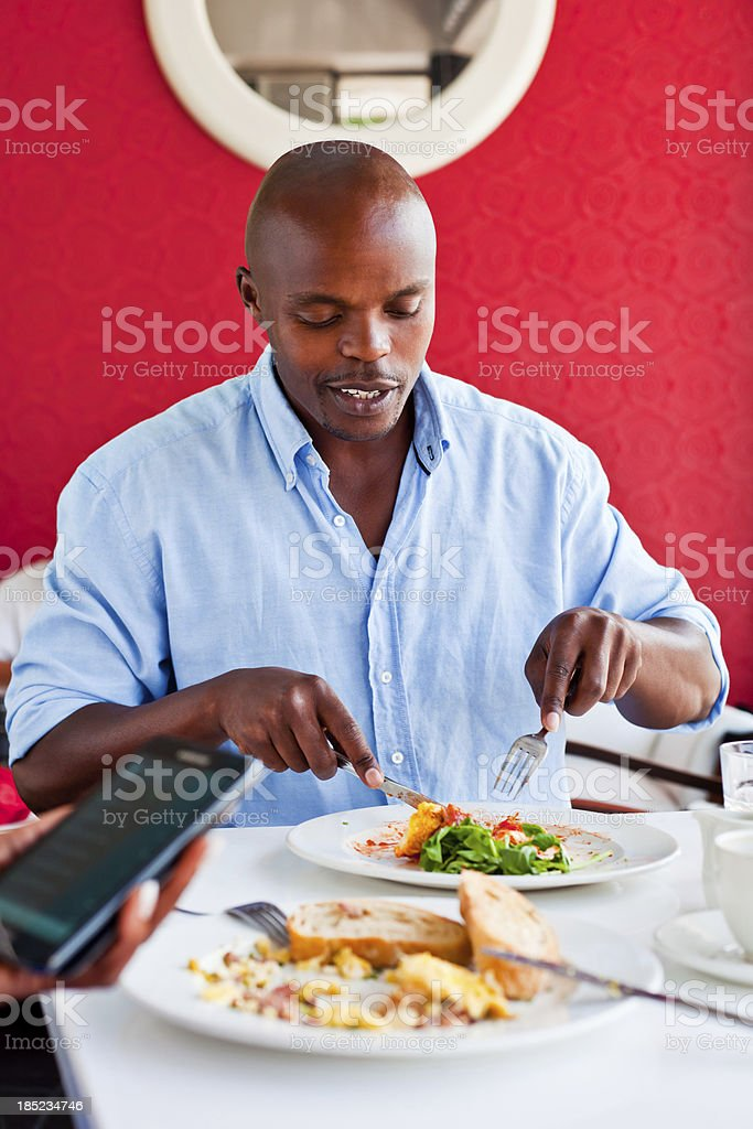Lunch time A handsome african man having lunch in the restaurant, while his friend using smart phone. Adult Stock Photo