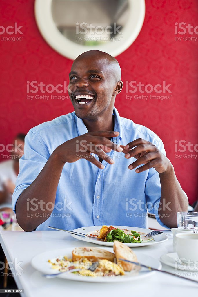 Lunch time A happy african man having lunch in the restaurant. Adult Stock Photo