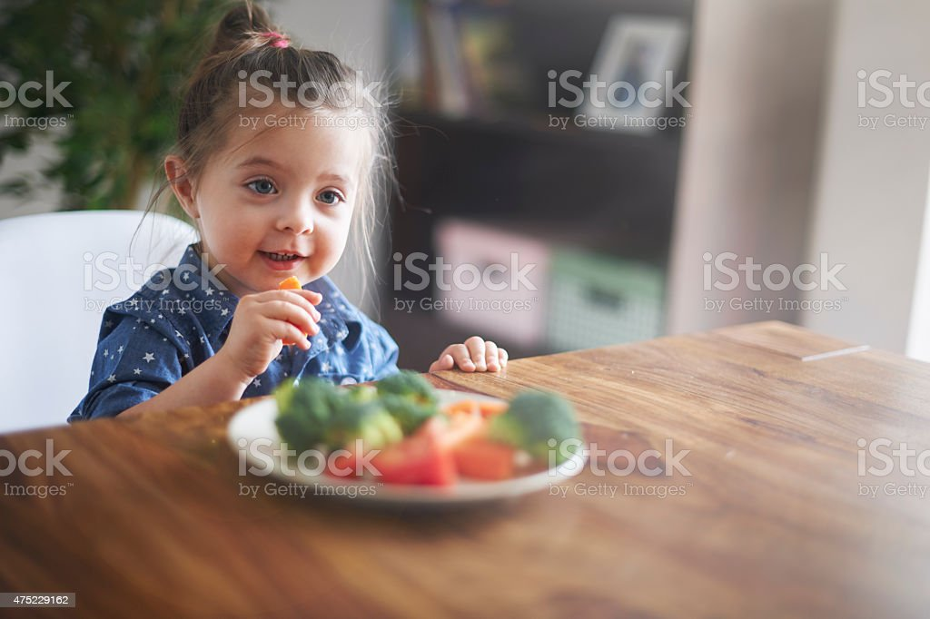Lunch time! She's eating a healthy vegetables stock photo